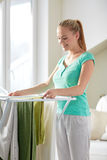 Happy woman hanging clothes on dryer at home Royalty Free Stock Images