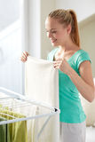 Happy woman hanging clothes on dryer at home Royalty Free Stock Photo