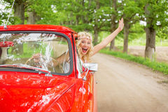 Happy  woman hanging out of vintage car Stock Photography