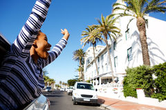 Happy woman hanging outside car window with arms raised Stock Photo