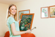 Happy woman hanging the  pictures Royalty Free Stock Photography