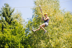 Happy Woman Hanging On Zip Line In Forest. Full length of happy young woman hanging on zip line against trees in forest stock photos