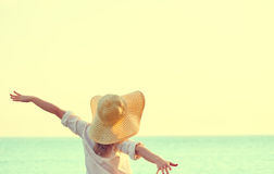 Happy woman in hat is back  opened his hands, enjoys sunset. Happy beauty woman in hat is back opened his hands, relaxes and enjoys the sunset over the sea on Stock Photo