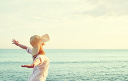 Happy woman in hat is back  opened his hands, enjoys sunset Royalty Free Stock Photography