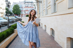 Happy woman in hat and blue dress in the city Stock Photography