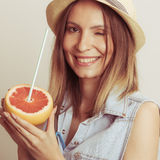 Happy woman in hat drinking grapefruit juice. Diet Royalty Free Stock Photography
