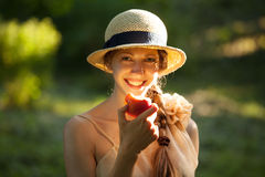 Happy woman in hat eating apple Stock Photo