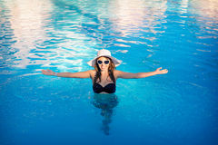 Happy woman with a hat floating in a swimming pool Royalty Free Stock Image
