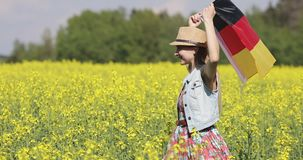 Happy woman in a hat with a German flag walks on a blooming rapeseed field in summer. Flag of Germany fluttering in the wind. Sunny weather stock footage
