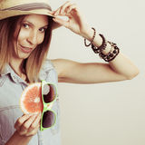 Happy woman in hat holds sunglasses and grapefruit Royalty Free Stock Image