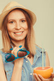 Happy woman in hat holds sunglasses and grapefruit Stock Photography