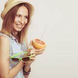 Happy woman in hat holds sunglasses and grapefruit Royalty Free Stock Images