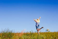 Happy woman in hat jumping in green field against blue sky stock image
