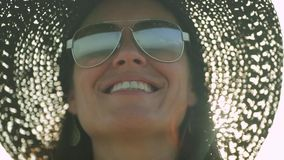 Happy woman with hat looking at ocean, reflection seen through her sunglasses stock footage