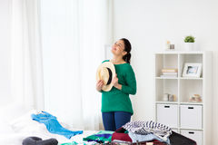 Happy woman with hat packing travel bag at home Royalty Free Stock Photos