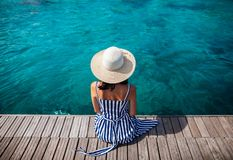 Happy woman in hat relaxing on sea pier in Sardinia island, Italy. Summer vacations concept royalty free stock images