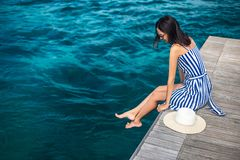 Happy woman in hat relaxing on sea pier in Sardinia island, Italy. Summer vacations concept stock photography
