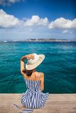 Happy woman in hat relaxing on sea pier in Sardinia island, Italy. Summer vacations concept royalty free stock photo