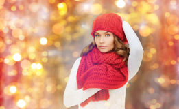 Happy woman in hat, scarf and pullover over lights. Winter, people, christmas and holidays concept - woman in hat, muffler and pullover over lights background Stock Photography