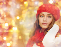 Happy woman in hat, scarf and pullover over lights. Winter, people, christmas and holidays concept - woman in hat, muffler and pullover over lights background Royalty Free Stock Images