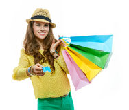 Happy woman in hat with shopping bags giving credit card royalty free stock photography