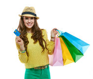Happy woman in hat with shopping bags showing credit card Royalty Free Stock Photos