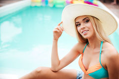 Happy woman in hat sitting near swiming pool. Happy gorgeous young woman in hat sitting near swiming pool Stock Images