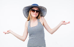 Happy woman in hat and sunglasses shrugging Stock Photo
