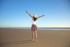 Happy woman with hat walking at beach Stock Photography