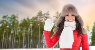 Happy woman in hat waving hand over winter forest royalty free stock images