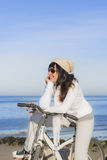 Happy woman having a break during a bike ride along the sea Royalty Free Stock Images