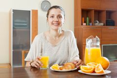Happy  woman having breakfast with croissants Stock Photos