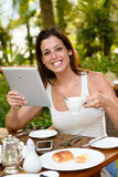 Happy woman having breakfast and using digital tablet Stock Image