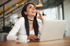 Happy woman having cell telephone conversation while sitting in Royalty Free Stock Photo