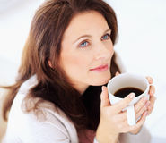 Happy woman having coffee , lost in thought Royalty Free Stock Images