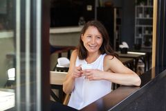 Happy woman having a drink of coffee at cafe Stock Photos