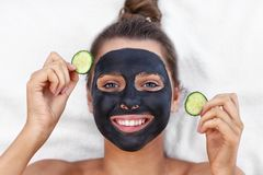 Happy woman having facial in spa salon stock photo
