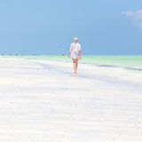 Happy woman having fun, enjoying summer, running along white tropical beach. Royalty Free Stock Photography