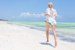 Happy woman having fun, enjoying summer, running joyfully on tropical beach. Royalty Free Stock Photo