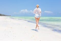 Happy woman having fun, enjoying summer, running joyfully on tropical beach. Royalty Free Stock Photos
