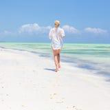 Happy woman having fun, enjoying summer, running joyfully on tropical beach. Stock Images