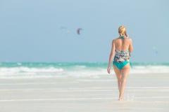 Happy woman having fun, enjoying summer, walking joyfully on tropical beach, Zanzibar, Tanzania. Royalty Free Stock Photo