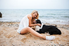 Happy woman having fun with her dog on the beach Royalty Free Stock Images
