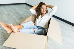 Happy american woman having fun laughing moving into new home. Young woman riding sitting in cardboard box playing while packing stock photos