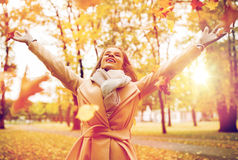 Happy woman having fun with leaves in autumn park Royalty Free Stock Image