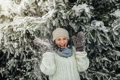 Happy woman having fun with snow falling from trees. Portrait of a laughing woman standing under a snowy tree and enjoying snow shower Royalty Free Stock Image