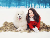 Happy woman having fun with white Samoyed dog outdoors on the snow in winter day Royalty Free Stock Image