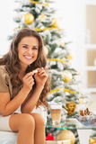 Happy woman having latte macchiato near christmas tree Stock Image