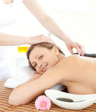 Happy woman having a massage with stones Stock Photo