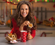 Happy woman having snack in christmas decorated kitchen Royalty Free Stock Image
